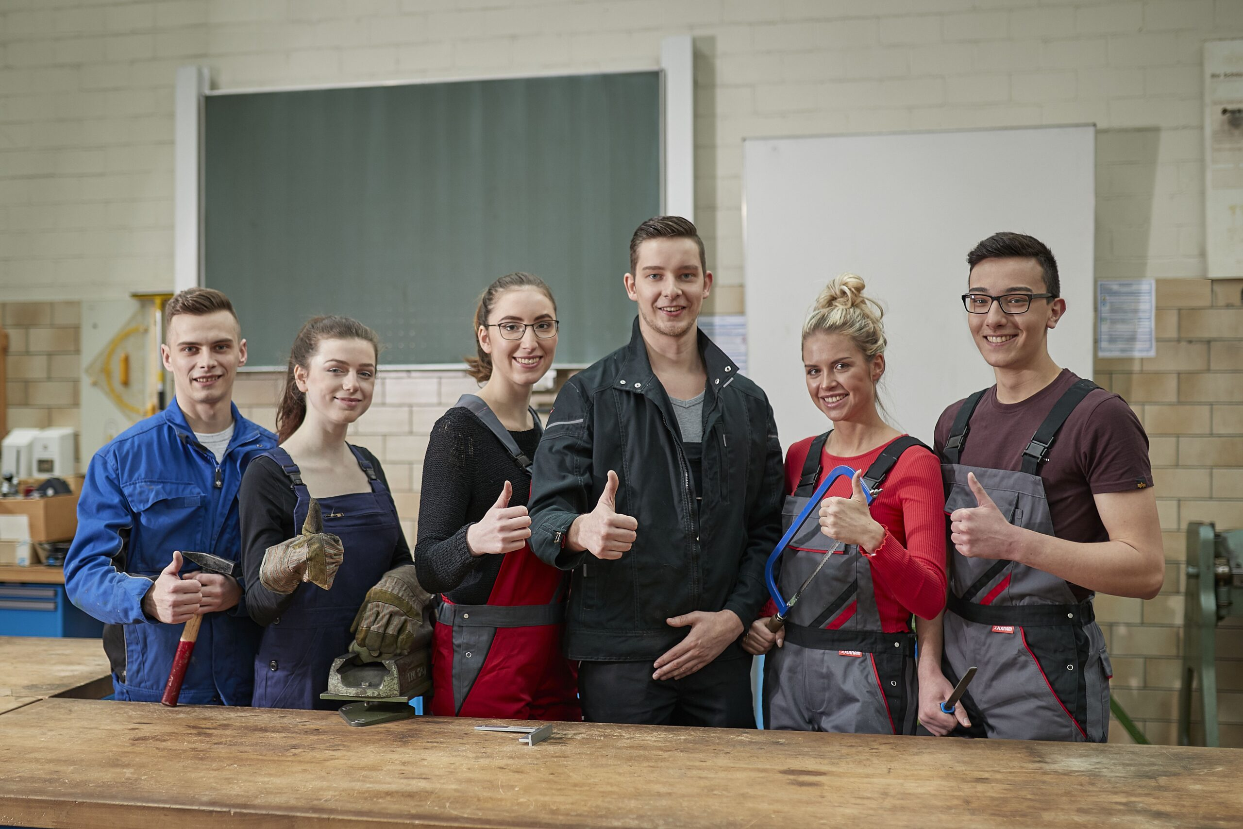 Sechs Jugendliche in der Werkstatt. Sie zeigen mit den Daumen nach oben und lächeln.