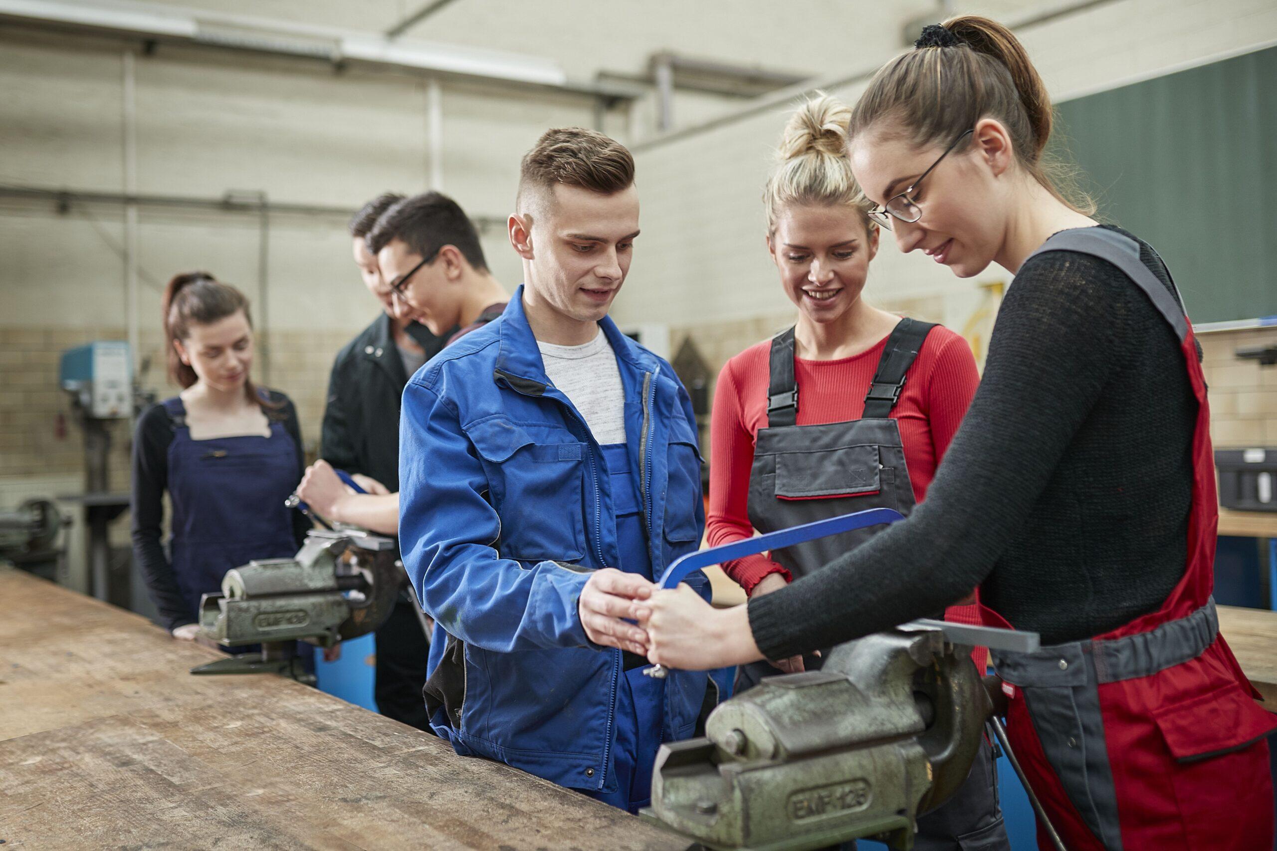 Auszubildende arbeiten an einem Metallstück
